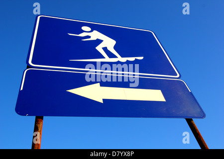 A BLUE AND WHITE SIGN INDICATING THE AREA SURFBOARDS ARE PERMITTED  TO BE RIDDEN AT THE BEACH BLUE SKY BACKGROUND - Stock Image