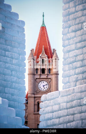 2018 Saint Paul Winter Carnival Ice Palace with Landmark Center clock tower. The ice palace was built in Rice Park downtown St. Paul, Minnesota. - Stock Image