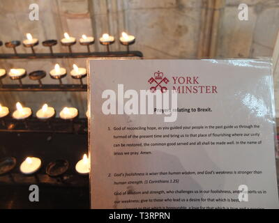 A selection of Prayers relating to Brexit on laminated card issued for visitors to York Minster UK. Backdrop of prayer candles. Brexit and religion. - Stock Image