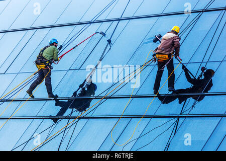 window cleaners at work on a glass facade, Czech Republic - Stock Image