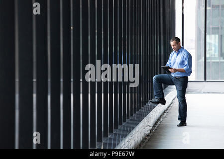 A Caucasian male architect standing by a wall of windows, using a digital tablet. - Stock Image
