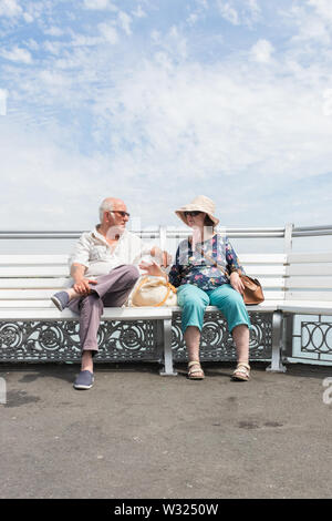 An elderly or retired couple relaxing sitting on a bench talking on a summers day - Stock Image