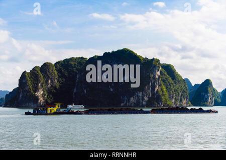 Working cargo boat transporting coal across Ha Long Bay in South China Sea. Quang Ninh province, Vietnam, southeast Asia - Stock Image
