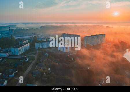 Dawn with fog in the sleeping area of a small town with a forest on the background. View from a height - Stock Image