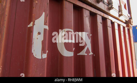 A Textainer shiiping container with the word tex scratched and chipped on the side - Stock Image