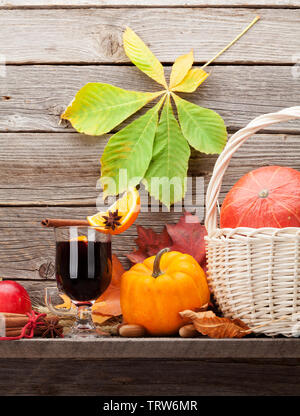 Autumn still life with mulled wine, pumpkins, apples, pears and colorful leaves in front of wooden wall - Stock Image