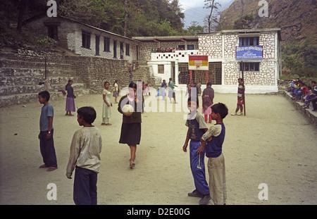 Teacher and students in playground of Shree Sarbodaya Secondary School near Tatopani in Kali Gandaki river valley - Stock Image