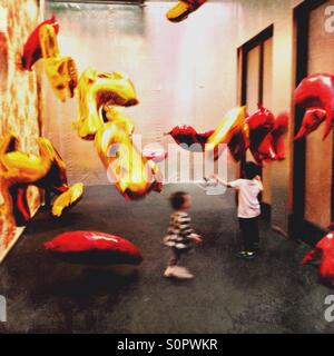 Children playing with animal shaped balloons - Stock Image