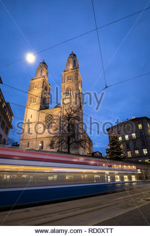 Zurich, Switzerland - view of the Grossmünster church with motion blurred tramway during Chrostmas time - Stock Image
