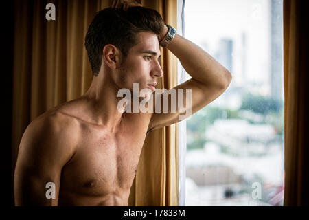 Sexy handsome young man standing shirtless in his bedroom next to window curtains - Stock Image