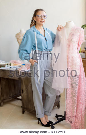 Portrait of confident fashionably dressed female tailor, shop owner standing at workplace leaning on dummy in pink lace fabric. - Stock Image