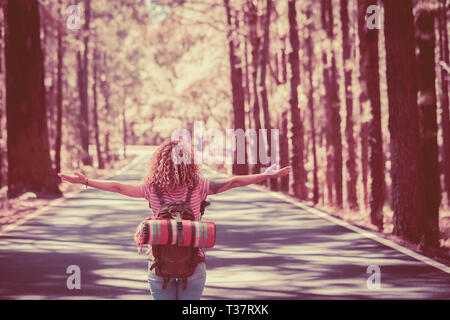 Cute curly traveler caucasian young woman viewed from back in the middle of the road with high trees on both sides opening arms and enjoying freedom a - Stock Image