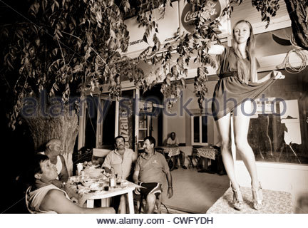 Young woman dancing on a table at a cafe in a Greek village while men cheer and applaud Greece - Stock Image
