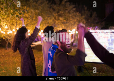 Happy friends cheering, watching sports in backyard - Stock Image
