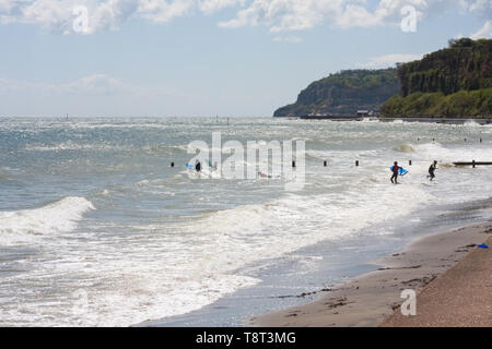 Young people enjoying bodyboarding in the sea between Shanklin and Sandown on the Isle of Wight - Stock Image