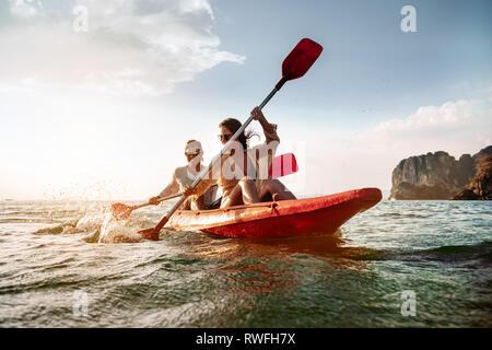 Happy couple walks by sea kayak or canoe at tropical bay - Stock Image