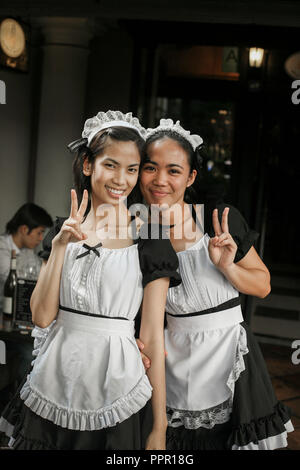 Two friendly waitresses in uniform pose for a photo in a Singapore restaurant - Stock Image