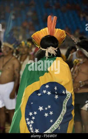 Palmas, Brtazil. 28th Oct, 2015. An indigenous protestor wears the Brazilian flag wrapped around him to demonstrate - Stock Image