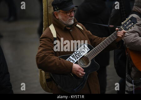 Vienna, Austria. 13th Jan, 2018. man playing guitar during an anti-government demonstration. the sticker reads 'this - Stock Image