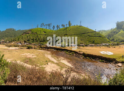 Horizontal panoramic view of a row of hillside cottages infront of a river in Munnar, India. - Stock Image