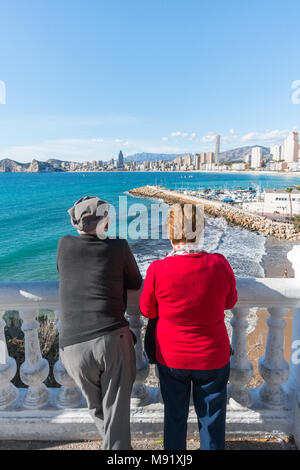 Elderly couple looking at the view of the sea and Poniente Beach and harbour in Benidorm, Spain. - Stock Image