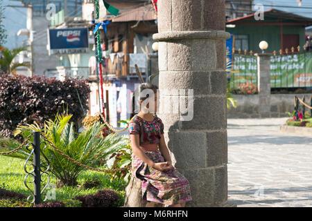 A young Tz'utujil Mayan girl sitting in a park in Santiago de Atitlán, Sololá Department, Guatemala. - Stock Image