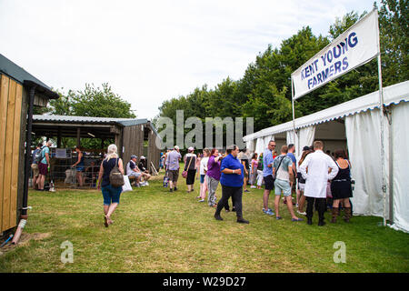 90th Kent County Show, Detling, 6th July 2019. People enjoying their day at the  Kent young farmers area of the agricultural show. - Stock Image