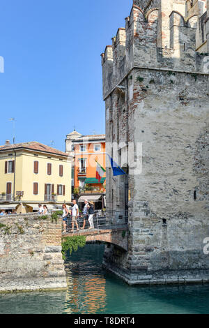 SIRMIONE, LAKE GARDA, ITALY - SEPTEMBER 2018: People crossing the bridge over the moat as they come out of Scaliger Castle in the centre of Sirmione o - Stock Image