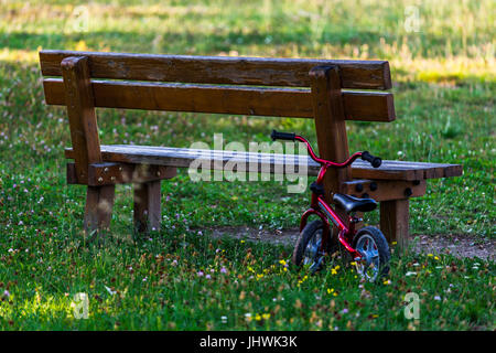 Wooden bench with a small bicycle for children standing on a meadow. - Stock Image