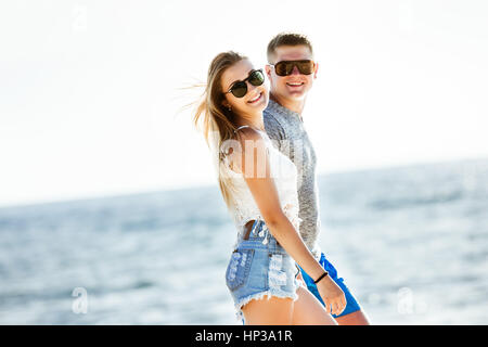 Happy couple beach walk sea - Stock Image