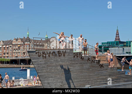 Boy jumping from the tower of Islands Brygge Harbour Bath in the beginning of the harbour bath season in Copenhagen, Denmark. Another warm summer day. - Stock Image