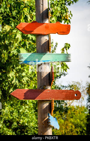 Wooden sign shaped like arrows showing directions in various colors - Stock Image
