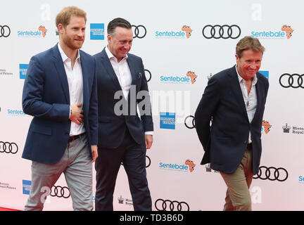 The Duke of Sussex (left) and John Hornby (right), chairman of Sentebale, arrive for a concert hosted by Sentebale in Hampton Court Palace in East Molesey, to raise awareness and vital funds for the Duke's charity, Sentebale, which helps young people in southern Africa affected by HIV. - Stock Image