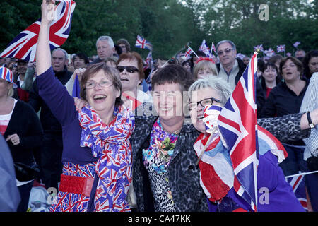 London, UK. June 4, 2012. Three fans in enjoy the Concert to celebrate The Queen's Diamond Jubilee on the big - Stock Image