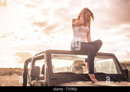 Thoughtful pretty young blonde caucasian girl sitting on his convertible car with nude feet - relax for a traveler with sunset cloudy sky in backgorun - Stock Image