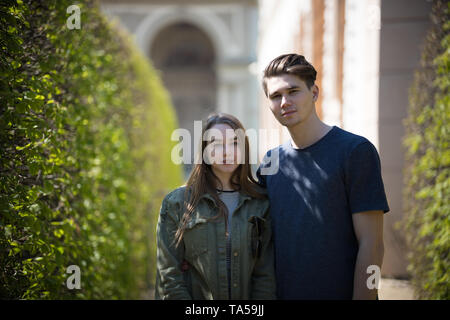 A young couple traveling. Standing on the street and looking in the camera. Mid shot - Stock Image