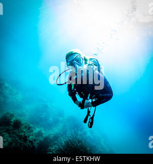 close up  of a young female diver near the surface while swimming over an eelgrass bed lit by rays of sunlight - Stock Image