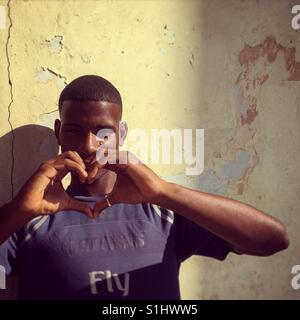 Young Cuban man making a heart shape with his hands - Stock Image