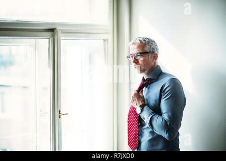 Mature businessman with glasses on a business trip standing in a hotel room, getting dressed. Copy space. - Stock Image