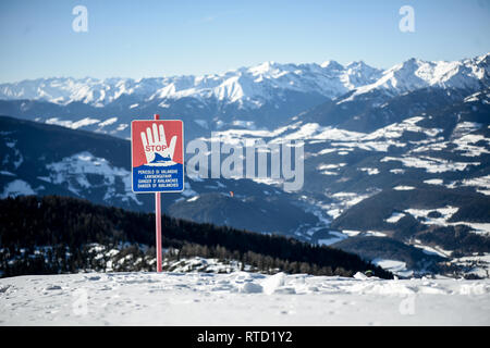 Kronplatz, South Tyrol, Italy - February 15, 2019: Danger of Avalanches warning  sign on snowy mountain slope in Kronplatz Plan de Corones ski resort  - Stock Image
