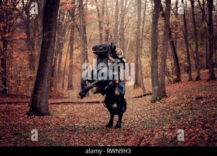 Medieval Warrior Man on a black horse standing on two legs. Reconstruction of a medieval war scene in the woods, in autumn. - Stock Image