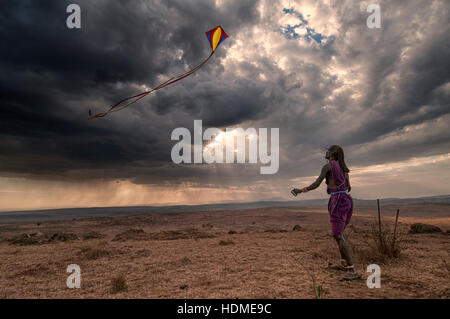 A Maasai Warrior flies a kite with dramatic sun beams and storm clouds. Scenic view, Kenya, Africa - Stock Image