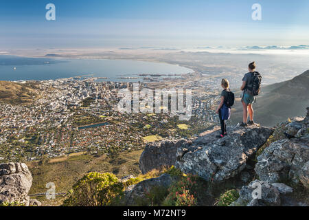 Two hikers admiring the view of Cape Town from a viewpoint along the India Venster hiking path on Table Mountain. - Stock Image