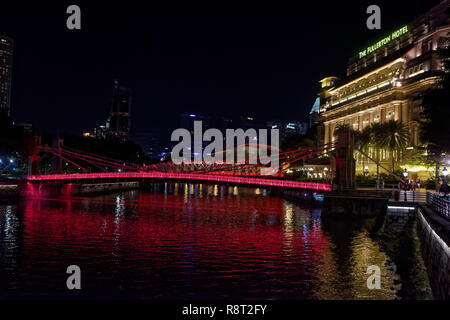 The Cavenaugh bridge, the only suspension bridge on the Singapore river, illuminated in red at night by the Fullerton Hotel - Stock Image