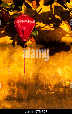 Red silk lantern on an ochre wall, late afternoon, Hoi An, Viet Nam - Stock Image