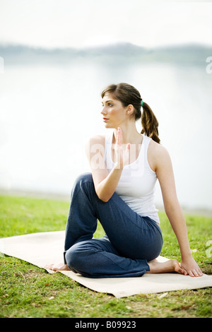 A young woman is practicing yoga in a park near a lake. - Stock Image