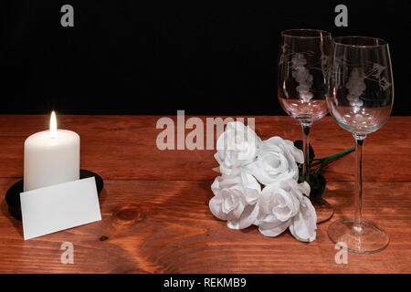Beautiful etched wine glasses with white roses and white candle and name tag on wooden table and dark background. Valentines, Mothers Day, Easter, Chr - Stock Image