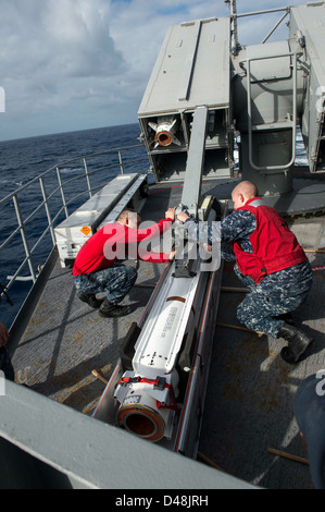 Sailors load a NATO Sea Sparrow missile at sea. - Stock Image
