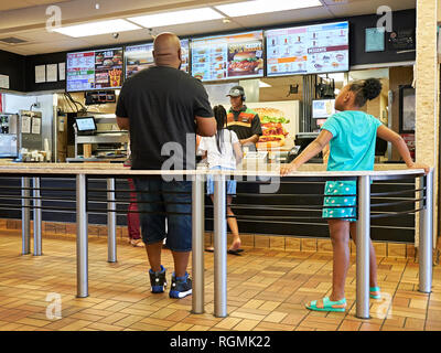Father or man and young girls being served inside in line at a Burger King fast food restaurant in Montgomery Alabama, USA. - Stock Image