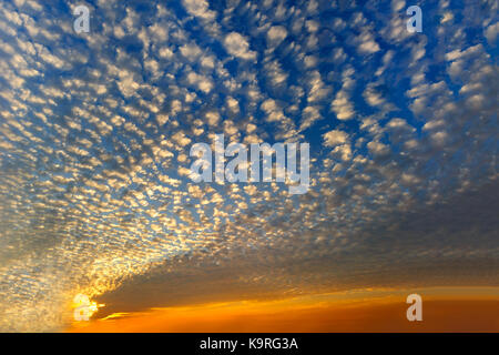 Sunset clouds is a sky filled with colorful patterned sunset clouds. - Stock Image